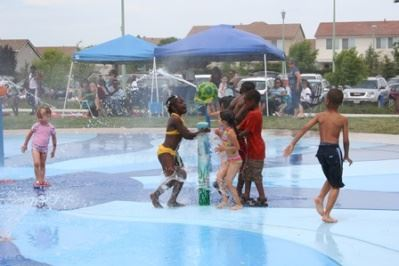 Children playing in a water feature at a sprayground park