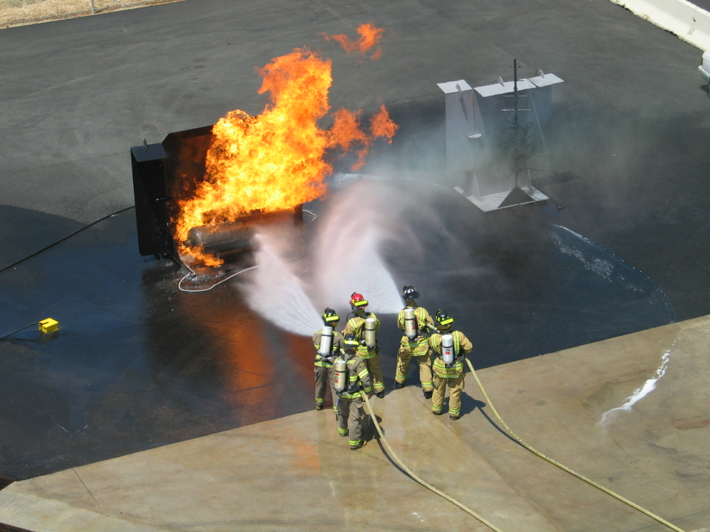 An aerial view of firefighters training to put out gas in a commerical building.