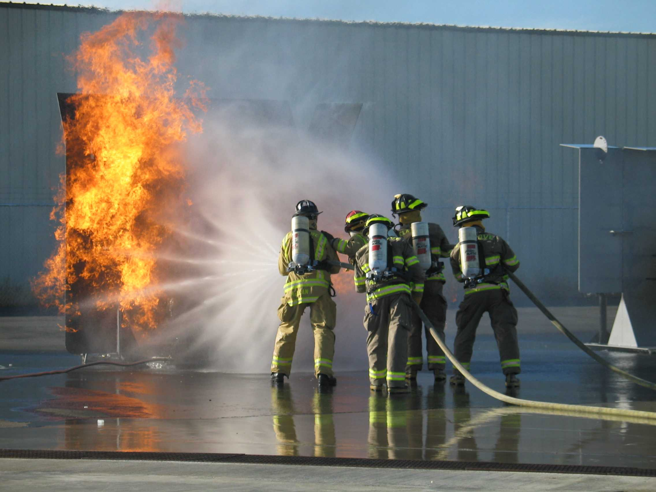5 firefighters train on putting out a fire.