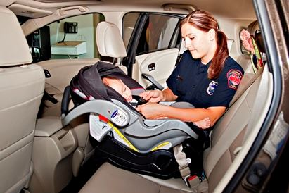 A Child Passenger Safety Technician checks a car seat to make sure it is installed properly.