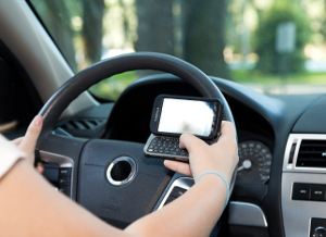 A photo of someone trying to text while driving.