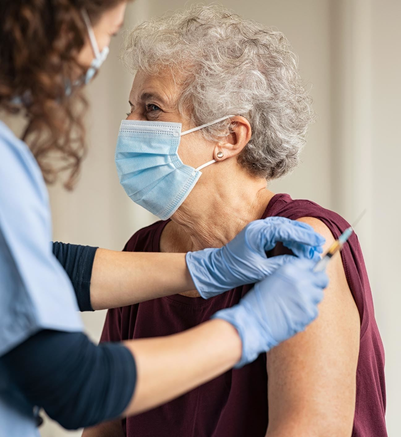 Doctor administering vaccine to elderly woman