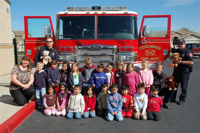 A group of students line up in front of a fire engine as firefighters hold teddy bears.