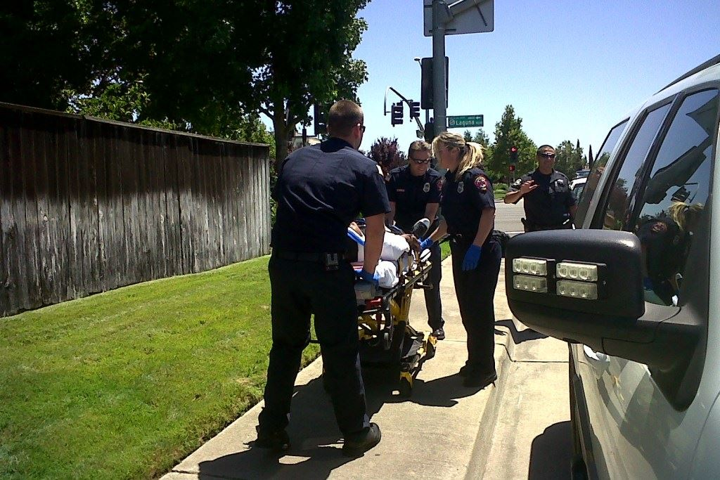 EMS workers help someone on a stretcher.