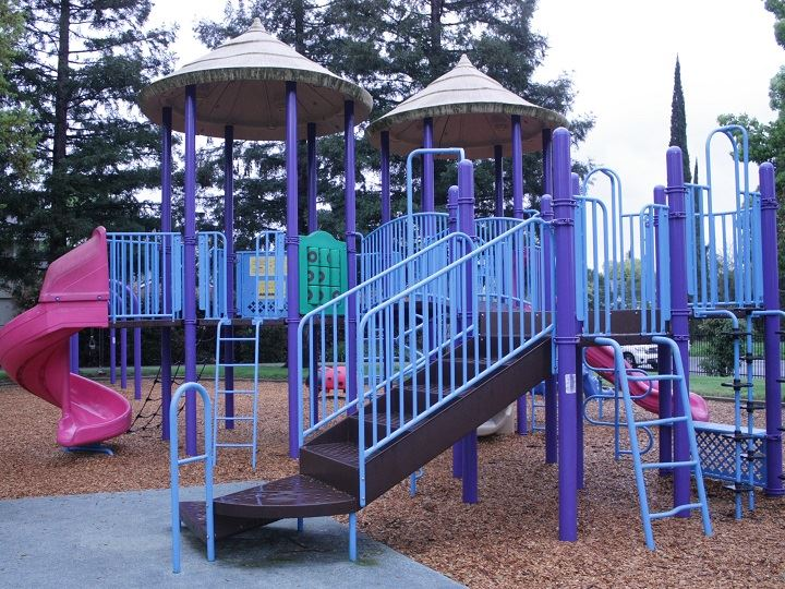 Play equipment in blue, with a pinkish-red slide and playground bark