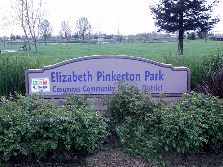 Pinkerton Park Sign with green shrubs and a dark cloudy sky