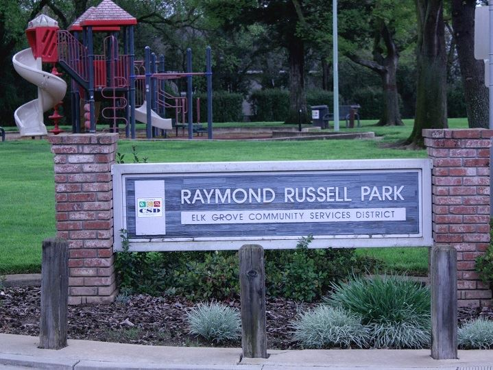 Russell Park sign with play area in background and green grass