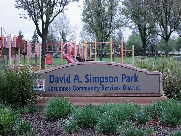 Park sign with green shrubs, trees and red and yellow playground in the background