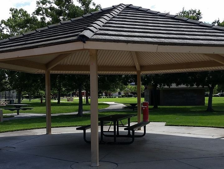Tan colored covered picnic area with 1 metal table underneath.  Trees and grass in the back ground.