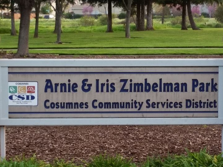 Arnie & Iris Zimbleman Park sign in a barked area with grass and trees in the background.